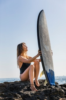 Blond woman sitting on rocky sea shore with surfboard