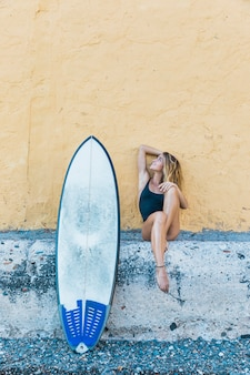 Blond woman sitting with surfboard leaning on wall