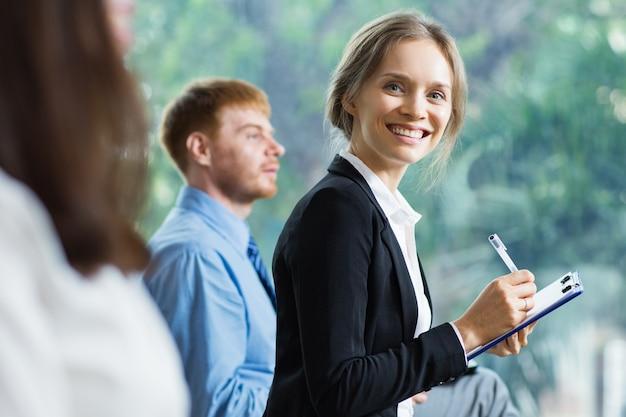 Donna bionda sorridente con una tavoletta grafica