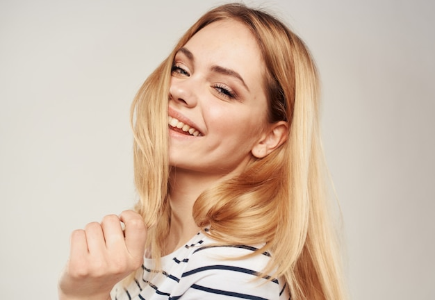 Blond woman in a striped tshirt on a beige background cropped view closeup