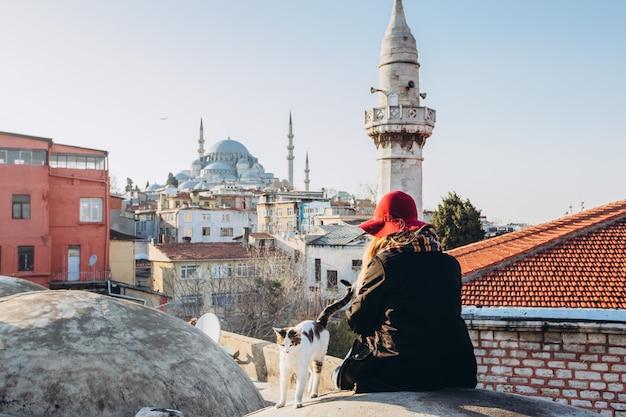Белокурая женщина поглаживая кота на крыше с целью мечети, стамбула, турции. девушка в шляпе сидит на крыше в стамбуле, солнечный осенний день. путешественник девушка гуляет по зимнему стамбулу.