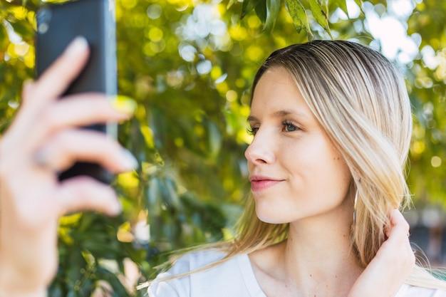 金髪の女性が屋外で自分撮りをします。ウェルネス、自然、アウトドアのコンセプト。