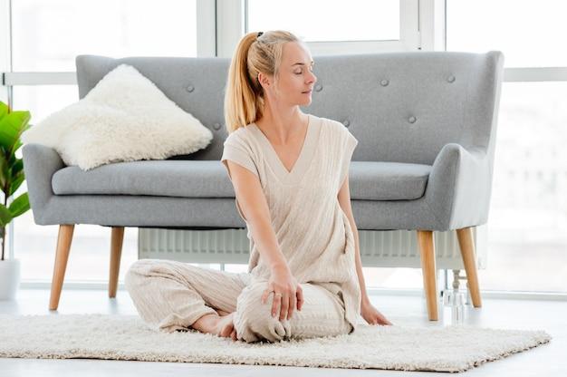 Блондинка повернулась на бок и растянула спину во время утренней йоги