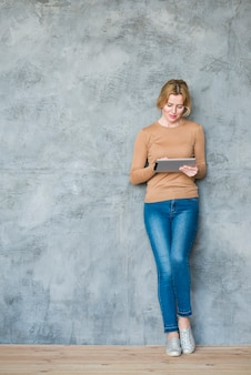 Blond woman using tablet at wall