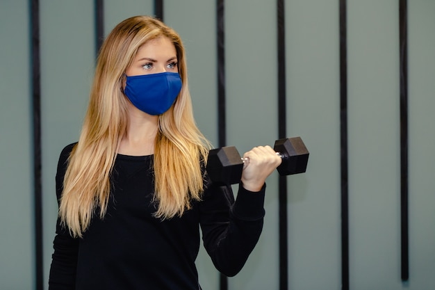 Blond woman wearing facial mask training in the gym during the pandemic.