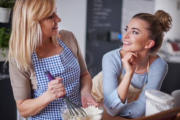 Donna bionda sbattere le uova e parlare con sua figlia