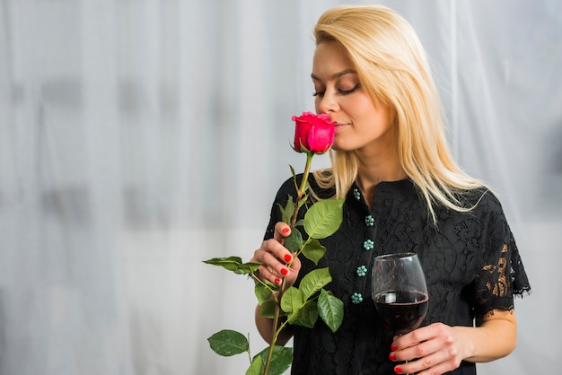 Blond woman with flower and glass of wine
