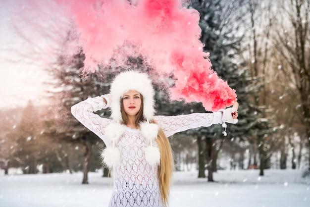 연기 폭탄을 들고 긴 머리를 가진 금발 여자
