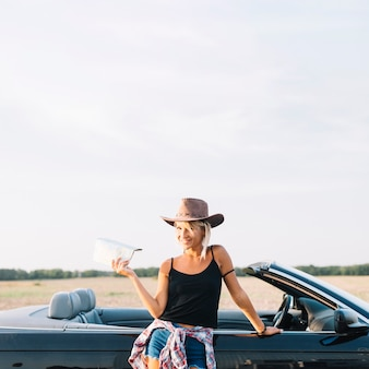 Blond woman with map near cabriolet