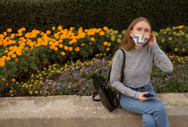 Blond woman with medical mask sitting next to a garden with copy space
