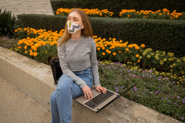 Blond woman with medical mask sitting next to a garden
