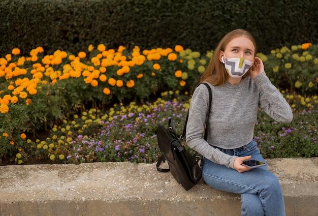 Блондинка с медицинской маской сидит рядом с садом с копией пространства