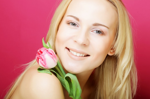 Блондинка женщина с розовым тюльпаном на розовом фоне