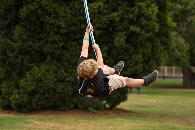 Blond young boy playing alone on a swing at a park