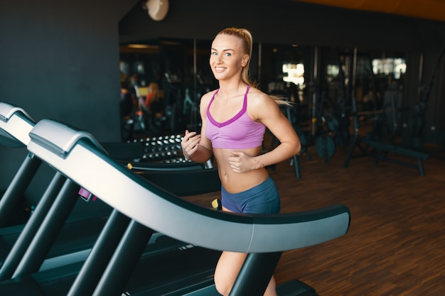 Blond young, motivated woman running on the treadmill