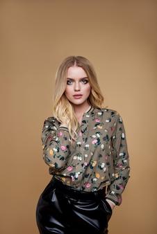 Белокурая молодая женщина в черных брюках и в весенней летней цветочной рубашке. девушка позирует на коричневой стене. летний цветочный наряд. стильная волнистая прическа. модное фото.