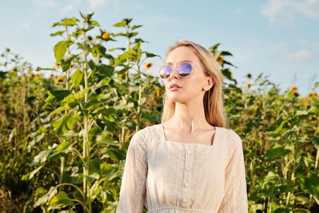 여름에 해바라기 밭과 푸른 하늘을 배경으로 카메라 앞에 서 있는 선글라스와 흰색 컨트리 스타일 드레스를 입은 금발의 젊은 여성
