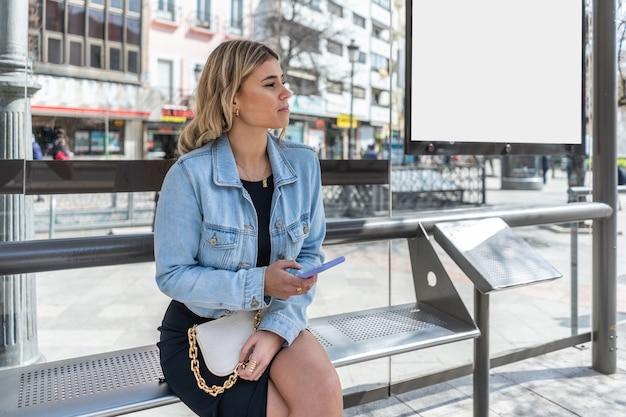 スマートフォンでバス停で待っている金髪の若い女性。モックアップ付き