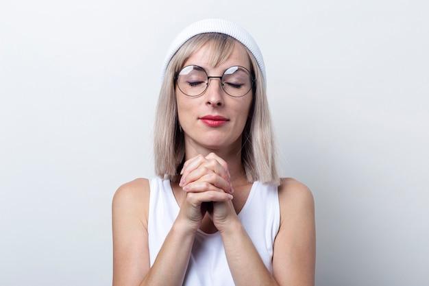 明るい背景に交差した指を保持している目を閉じて金髪の若い女性。