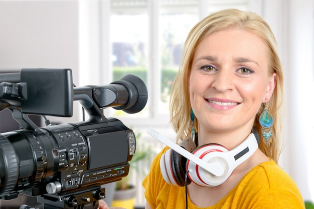 Blond young woman with professional video camera