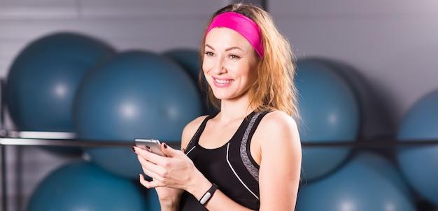 ジムでスマートフォンを持っている金髪の若い女性、トレーニング休憩