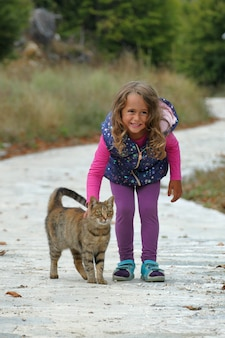 Blonde 4 year old girl caresses a kitten