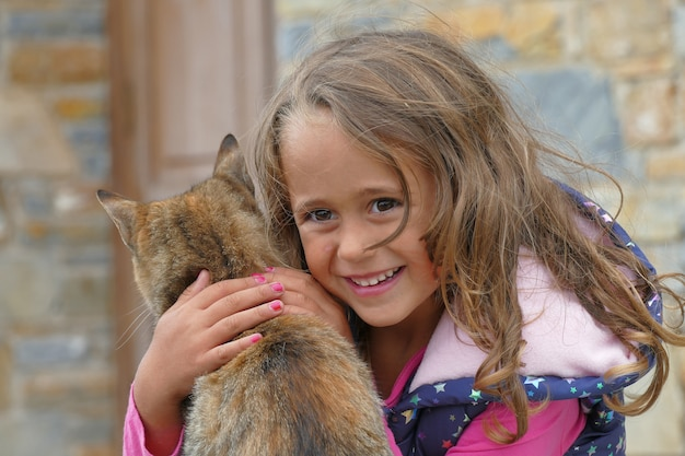 Blonde 4 year old girl embraces a kitten