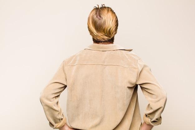 혼란 스럽거나 전체 또는 의심과 질문을 느끼는 금발 성인 백인 남자, 엉덩이에 손, 후면보기