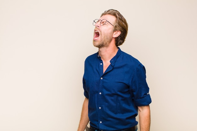 Blonde adult caucasian man screaming furiously, shouting aggressively, looking stressed and angry