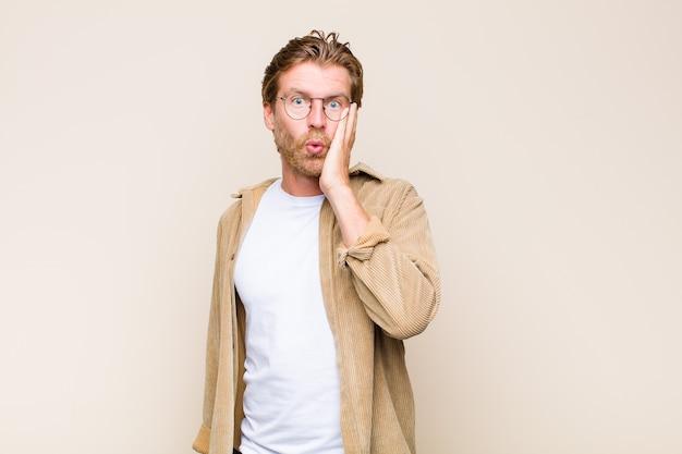 金髪の大人のコーカサス人は、口を大きく開いた状態で不信感を抱きながら、ショックを受けて驚いた。