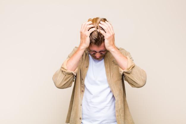 ストレスと欲求不満を感じ、手を頭に上げ、疲れ、不幸、片頭痛を感じている金髪の大人のコーカサス人