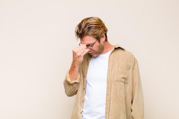 ストレス、不幸、欲求不満を感じ、額に触れ、激しい頭痛の片頭痛に苦しんでいる金髪の成人コーカサス人
