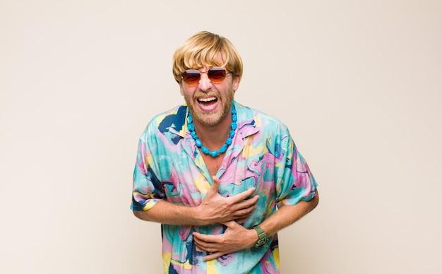 いくつかの陽気な冗談で大声で笑って、幸せで陽気に感じて、楽しんでいる金髪の大人のコーカサス人
