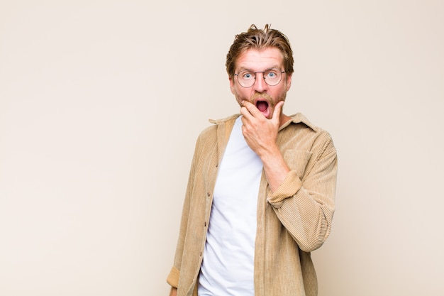 Blonde adult caucasic man with mouth and eyes wide open and hand on chin, feeling unpleasantly shocked, saying what or wow