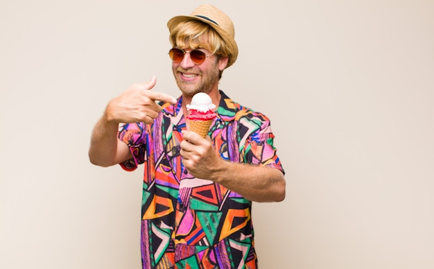 帽子とサングラスとアイスクリームを保持している金髪の成人男性