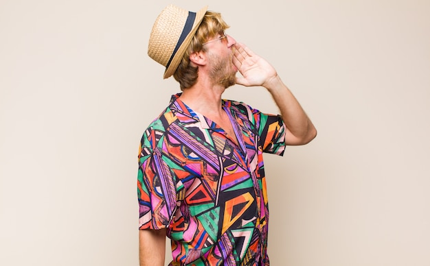 Blonde adult traveller man profile view, looking happy and excited, shouting and calling to copy space on the side