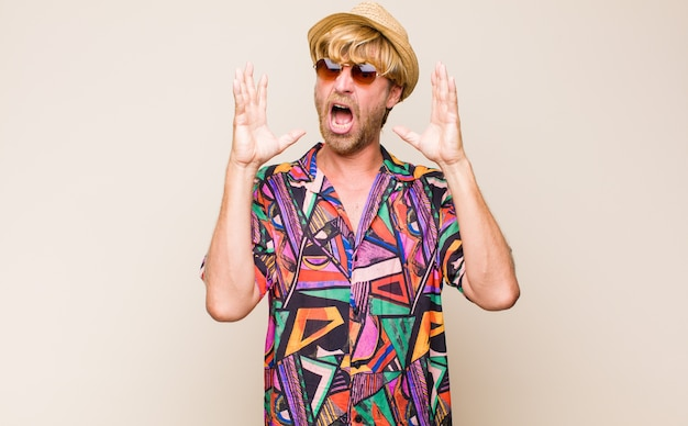 Blonde adult traveller man screaming with hands up in the air