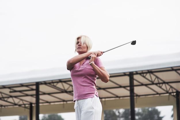 히트 후 스틱을 잡고 골프 공을 추적 금발 성인 여자.