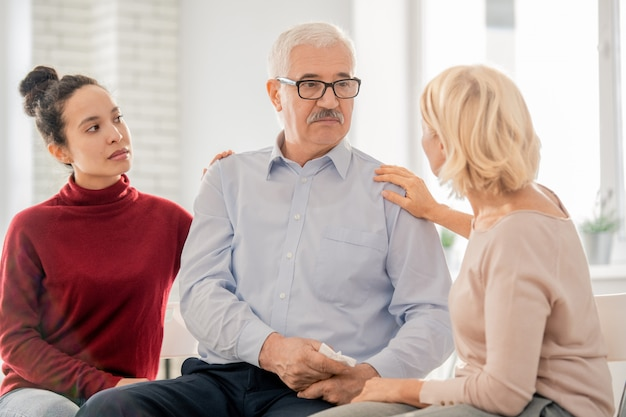 Blonde aged woman and mixed-race girl reassuring senior groupmate or patient during psychotherapy session