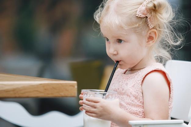 Блондинка и молочный коктейль за столиком на городской улице