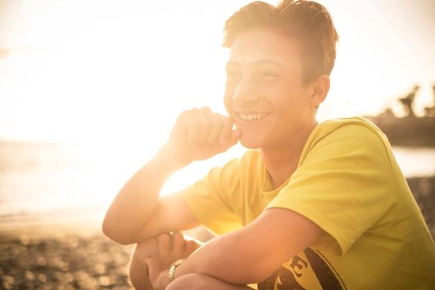 テネリフェ島カナリア諸島の背景に太陽と夕日のある14歳の金髪で美しいティーンエイジャー。若いモデルは自由とビーチを楽しむ