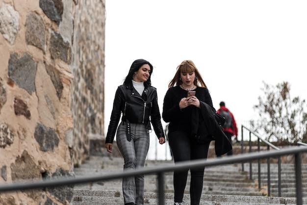금발 머리와 갈색 머리 소녀는 도시에서 계단을 걷고있는 동안 휴대 전화를보고.
