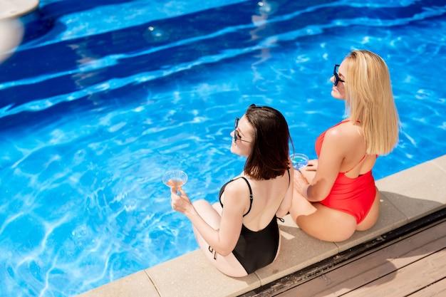 飲み物とスイミングプールのそばに座っている水着のブロンドとブルネットの女の子