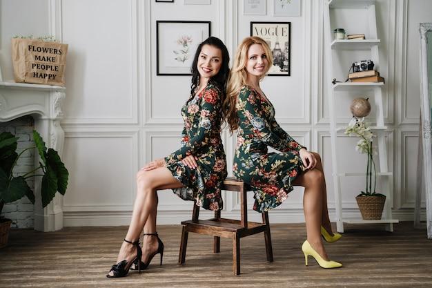 Блондинка и брюнетка в коротких зеленых платьях с узорами. две красивые девушки в белой студии.