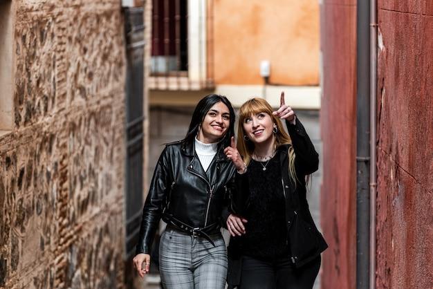 금발 머리와 갈색 머리 여자는 오래 된 도시 거리에 관광