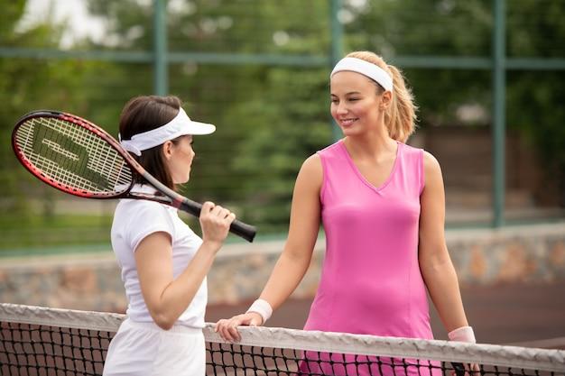 スタジアムでのテニスの試合後にネットで相互作用するブロンドとブルネットの若い女性