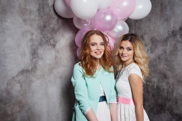 Блондинка и рыжий. две молодые очаровательные женщины на вечеринке. счастливая и жизнерадостная женщина с воздушными шарами.