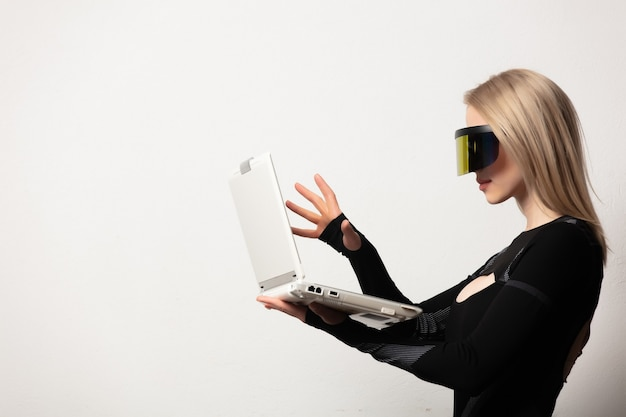 Blonde android female in vr glasses and laptop on white background.