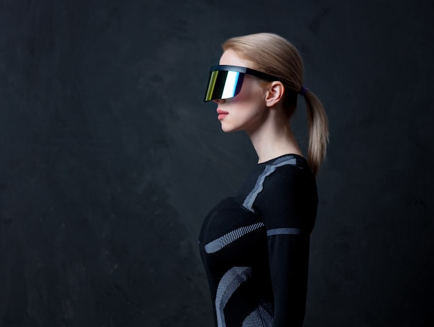 Blonde android female in vr glasses and suit on dark background.