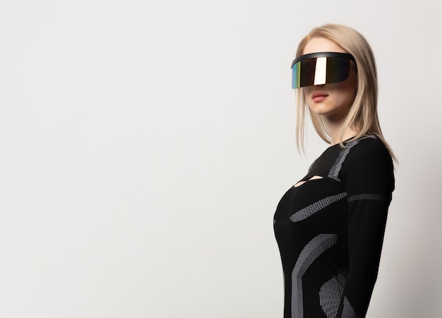 Blonde android female in vr glasses and suit on white background.